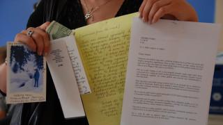 Eine Teilnehmerin des Women-for-Women- International-Programms zeigt die Briefe, die sie von ihrer Patin erhalten hat.