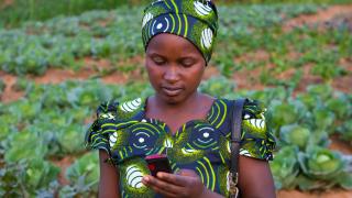 Eugenie, eine Programmabsolventin aus Ruanda, bezahlt ihre Rechnungen mit mobilem Banking. Foto: Alison Wright